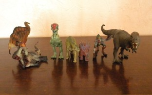 De gauche à droite : acrocanthosaure et sa victime (Rebor), Pachycéphalosaure (Jurassic Park), Camarasaurus (marque inconnue), Styracosaure (marque inconnue), Vélociraptor (Bullyland), T-Rex (Bullyland). Crédit : Chris Bellabas