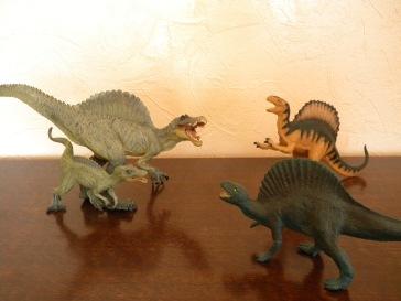 À gauche : adulte et bébé spinosaures Papo. À droite : spinosaure Schleich (premier plan), spinosaure Safari (second plan).