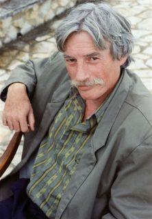 Jean Ferrat assis sur une chaise.
